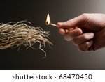 male hand holding a match in the act of lighting a tuft of straw - stock photo