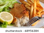 A dinner of fish and chips (or french fries) served with a salad of garden-fresh lettuce, rocket and tomato and a piece of lemon - stock photo