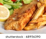 A piece of fish in batter served with french fried potato chips, lemon and a lettuce, rocket, cucumber and tomato salad. - stock photo