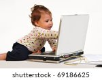 Baby sitting on desk, playing with laptop pointing at screen - stock photo