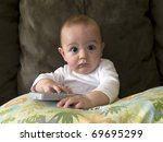 An infant child plays with a remote control - stock photo