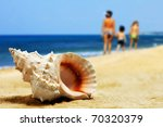 seashell on the sand and mother with children. - stock photo