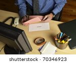 business man at desk holding pink slip - stock photo