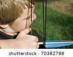 Close up of a boy ready to pull the bow to shoot and arrow. - stock photo