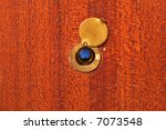 Peephole on peeling wooden door - stock photo