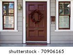 Home burgundy door with wreath with two white trimmed blinded windows - stock photo