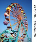 A ferris wheel with colorful cabins at a local fun fair - stock photo