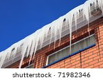 The ice on the roof of the brick house - stock photo