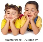 kids lying on stomach, leaning on elbows, chin in hands, looking down - stock photo