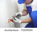 Electrician stripping electrical wires for wall socket - stock photo