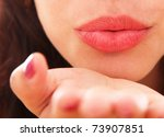 Beautiful woman of lips blowing on his hand - stock photo