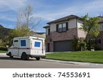Mail truck makes a stop in a residential neighborhood. - stock photo