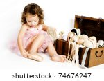 Little brunette girl trying on ballet shoes - stock photo