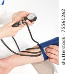 Nurse measuring the blood pressure - stock photo