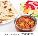 A bowl of kadai paneer (cheese) curry with naan bread and a side salad. - stock photo
