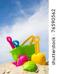 Child's bucket, spade and other toys on tropical beach against blue sky - stock photo