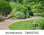A stone walkway through a peaceful perennial garden. - stock photo