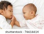portrait of cute ethnic little girl playing with baby in bed - stock photo