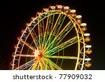 Amusement park at night - ferris wheel and rollercoaster in motion - stock photo