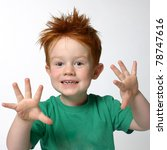 Young cute cheeky boy with spikey red hair, holding hands up with five fingers wearing green t shirt - stock photo