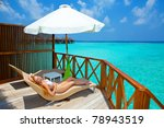 Young woman on chaise lounge under parasol near the sea. Maldives. - stock photo