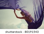 Beautiful blonde girl in a blue dress standing in the wind against the sky - stock photo