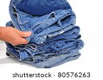 Man inspecting a pair of jeans on top of the stack - stock photo
