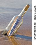 save the date message in a bottle stuck in beach sand - stock photo