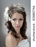 portrait of beautiful bride with flowers in hair on grey - stock photo