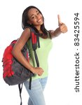 Thumbs up happy success for pretty young African American teenager school girl, with long black hair wearing green t-shirt and red school backpack with beautiful smile. - stock photo