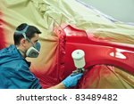 Man painting a red car. - stock photo