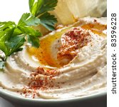 Bowl of hummus topped with paprika.  Traditional chickpea dip. - stock photo