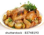 Whole roasted chicken with potatoes and herbs on white plate - stock photo