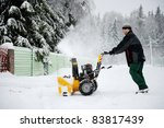 A man is cleaning the country road with snow blower in winter - stock photo