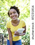 A pretty african american woman with a book at the park - stock photo