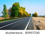 long asphalt road and autumn trees on sky background - stock photo