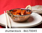 A typical Indian take away of Chicken Tikka Masala with naan breads. - stock photo