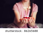 Close-up photo of a cupcake with five lighted candles in child's hands, focus on a cupcake - stock photo