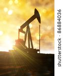 Conceptual image of a land based oil well pump machine with sun flaring from behind it. - stock photo