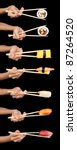 Set of 7 hands holding various types of sushi with chopsticks isolated on a black background. - stock photo