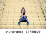 Beautiful hippie girl sitting on a vintage stairs in autumn scenery wearing maxi long dress and gorgeous make up. - stock photo