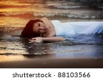 Attractive young woman in wedding dress enjoys sea water during the sunset - stock photo