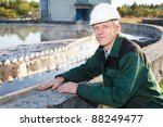 Mature man manual worker in white hardhat near sewage treatment basin - stock photo