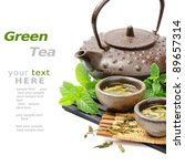 Asian tea set with dried green tea and fresh mint - stock photo