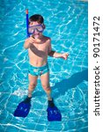 A little boy standing in a pool with a swimming mask and snorkel - stock photo