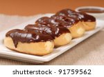 Delicious homemade eclairs with a chocolate ganache and dipping sauce - stock photo