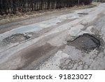 Damaged asphalt pavement road with potholes caused by freeze and thaw cycle during winter. - stock photo