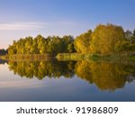 view of lake and trees reflecting from water - stock photo