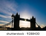 London landmark bridge- famous profile silhouetted against blue sky - stock photo