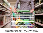 Female customer shopping at supermarket with trolley - stock photo